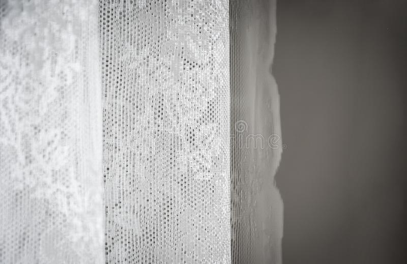 White curtain decorated with sewed floral pattern in lace. Interior shot with natural soft light stock photography