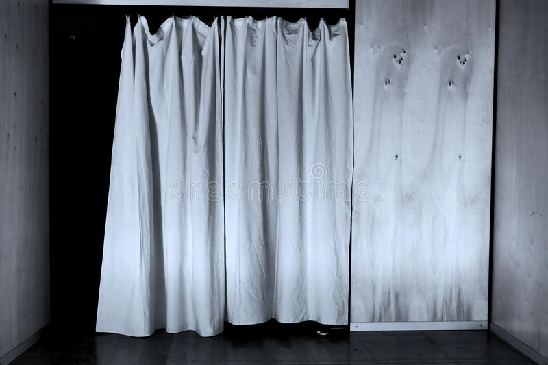 White curtain closed over doorway on a wooden wall black and white image stock images
