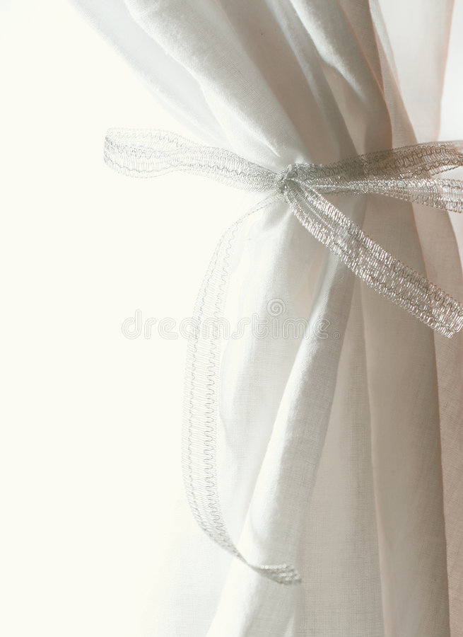 White curtains. Drawn back on white background royalty free stock photography