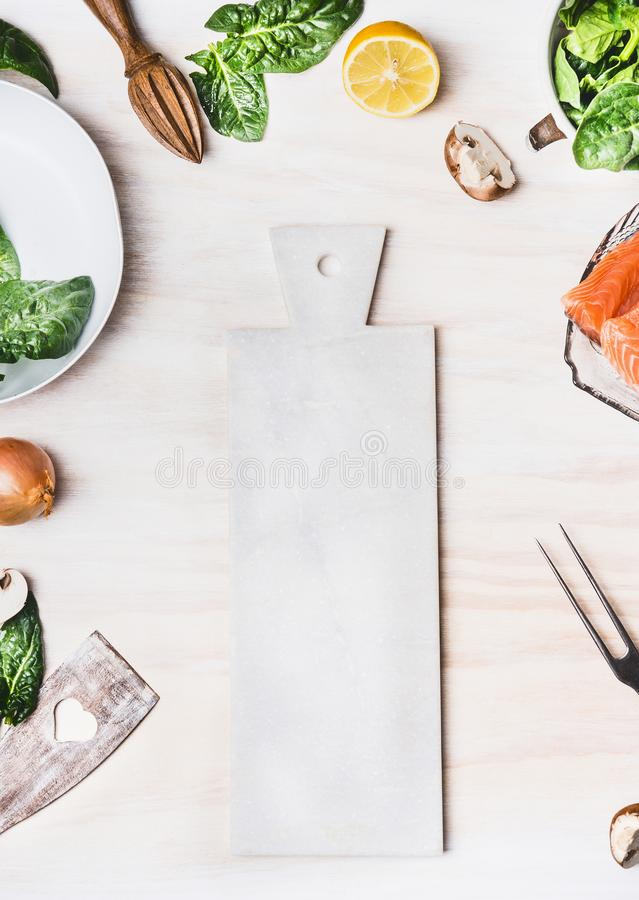 White cutting board on kitchen table background with Healthy food ingredients and tools, top view, frame. Clean eating and cooking royalty free stock photography