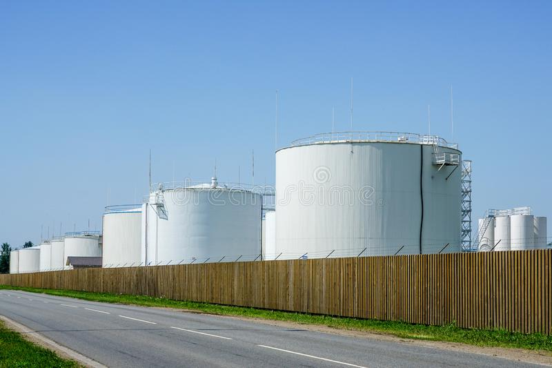 White cylindrical storage tanks for petroleum products. Against a blue sky stock photography