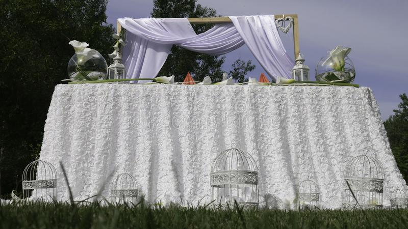 White decoration of the wedding - arch and table covered with white decoration for the wedding ceremony in the green garden stock images