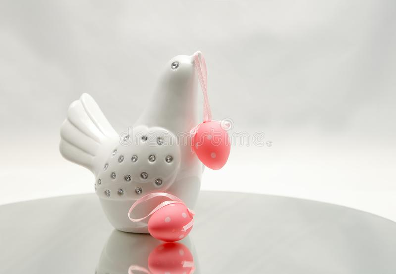 A white easter bird with two pink easter eggs. A white decorative bird with colourful Easter eggs. One hanging on its beak stock photos