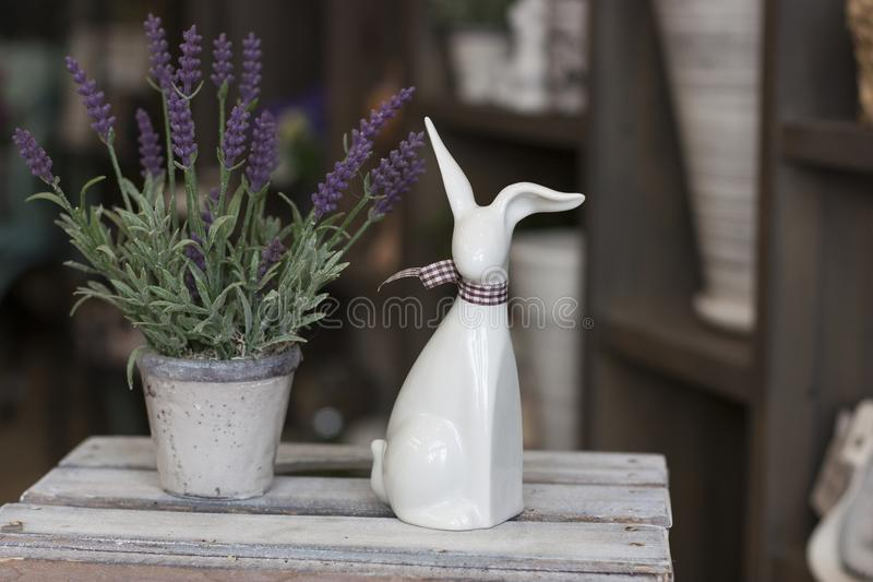 White decorative ceramic hare stands next to a pot of lavender royalty free stock images