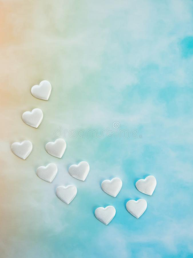 White decorative hearts on yellow and blue gradient background, copy space, top view. Love and Valentine`s Day backdrop.  royalty free stock photos