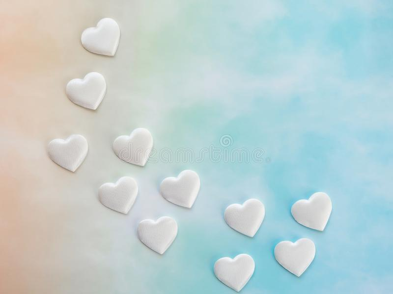 White decorative hearts on yellow and blue gradient background, copy space, top view. Love and Valentine`s Day backdrop.  stock images