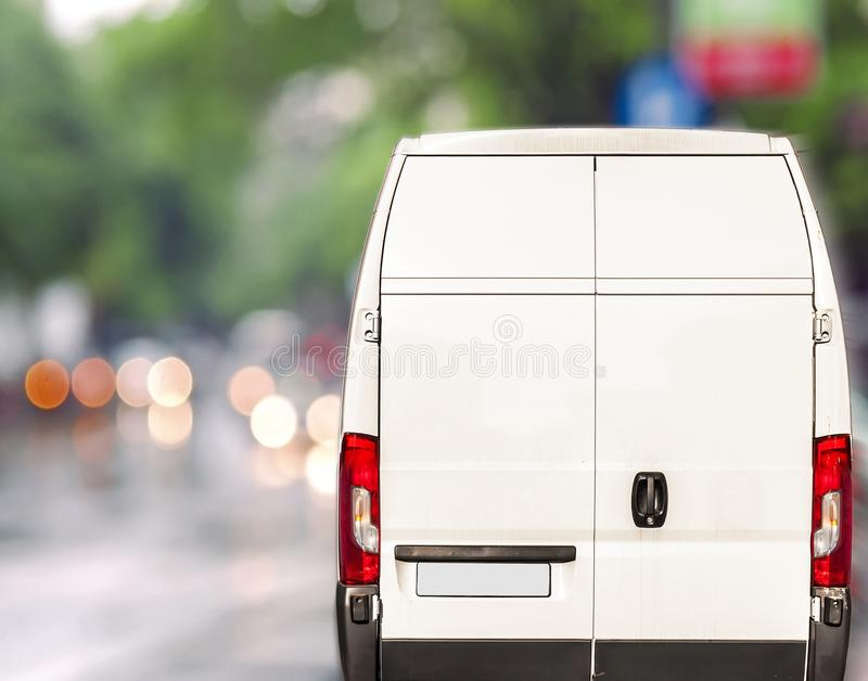 White delivery Van driving fast on city blurr bokeh street. Close stock image