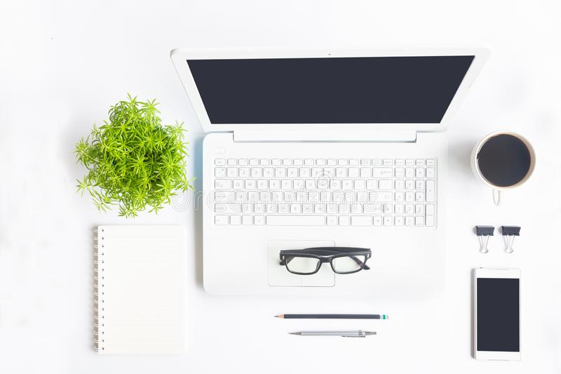 White desk office with laptop, smartphone and other work supplies with cup of coffee. Top view with copy space for input the text. Designer workspace on desk stock photo