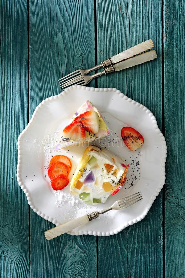Cold creamy cheesecake with fruit jelly and fresh strawberry. On white dessert plate there is a piece of cold creamy cheesecake with fruit jelly and fresh royalty free stock photos