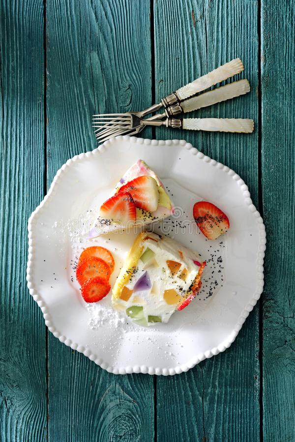 Cold creamy cheesecake with fruit jelly and fresh strawberry. On white dessert plate there is a piece of cold creamy cheesecake with fruit jelly and fresh stock photography