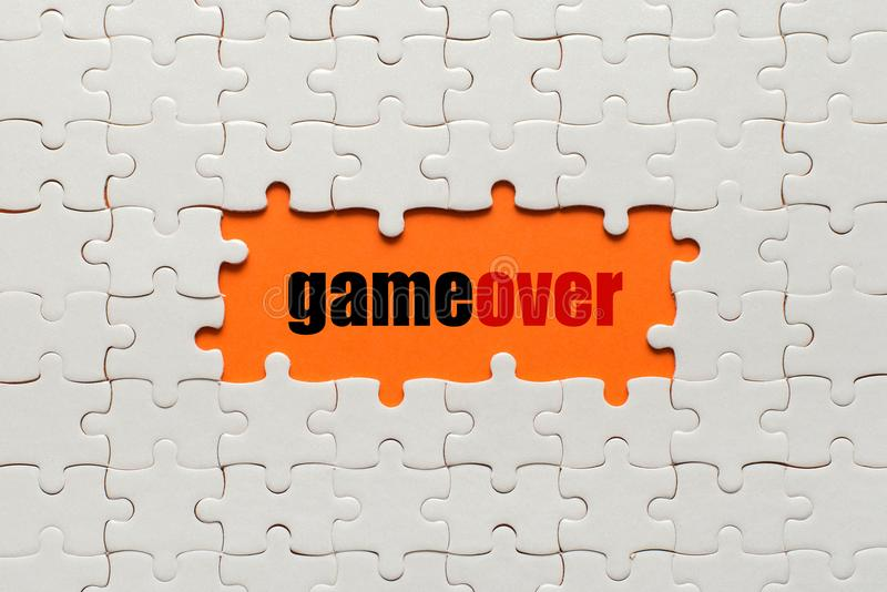 White details of puzzle on orange background and text Game Over royalty free stock image