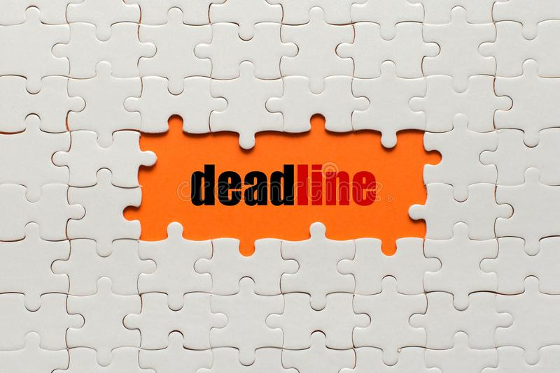White details of puzzle on orange background and word Deadline stock images