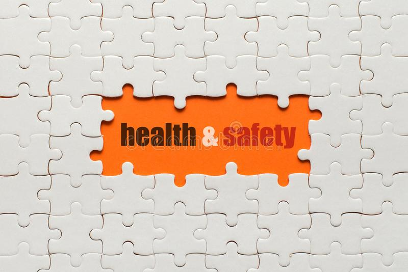 White details of puzzle on orange background and word Health and safety royalty free stock photos
