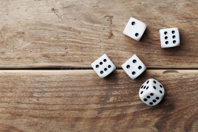 White dice on wooden table top view. Gambling devices. Game of chance concept. stock photography