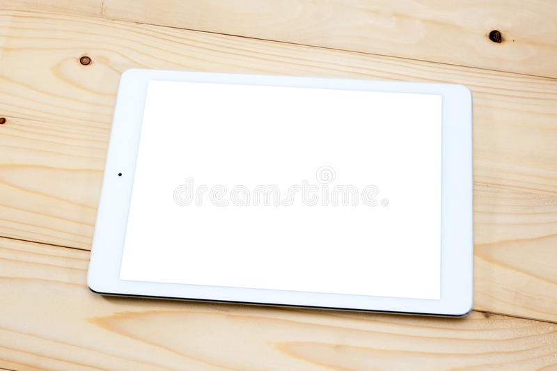 White digital tablet on wooden table royalty free stock image