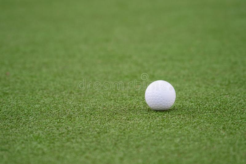 White dimple hockey ball on astro turf.  royalty free stock images