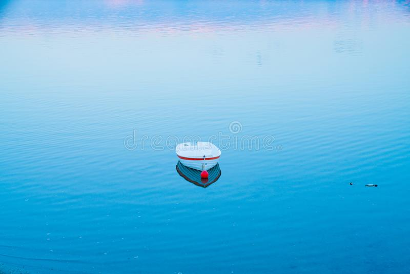 White dinghy afloat on calm blue water with reflection of sunset colors. In tranquil scene stock photos