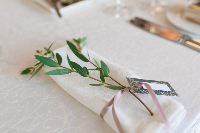 White dining napkin, tied with a dusty pink ribbon with branches of eucalyptus in the serving of the wedding Banquet royalty free stock photos