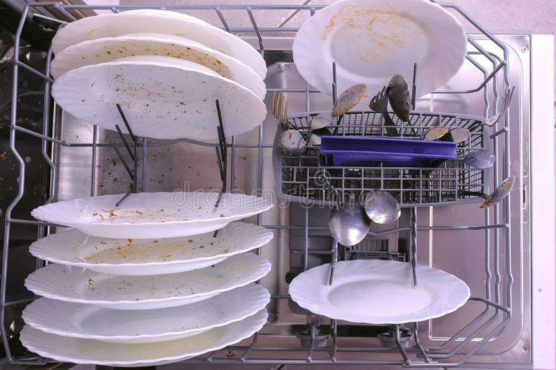 White dirty plates and spoon in dishwasher basket. Top view, close-up hand royalty free stock photo