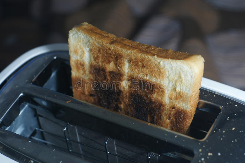White dirty toaster and burned toast (selective focus,dark tone) royalty free stock photography
