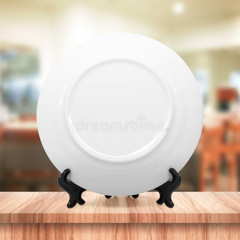 White dish or ceramic plate on modern kitchen background with blank dishware concept. White dish template place on wooden table royalty free stock image