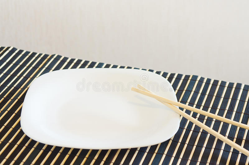 White Dish And Chopsticks On A Bamboo Table Cloth Stock Photos