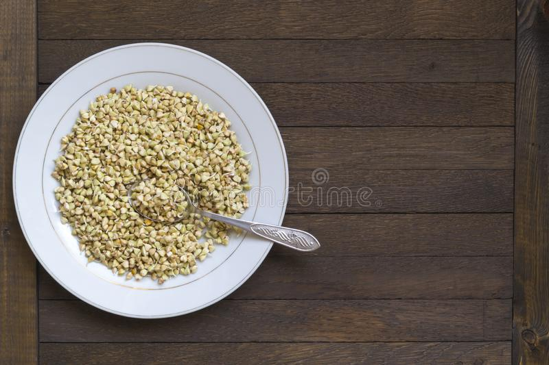 White dish with sprouted buckwheat and spoon inside on wooden table. Left position. Top view. Organic raw hulled groats. Background with copy space. Concept of royalty free stock image