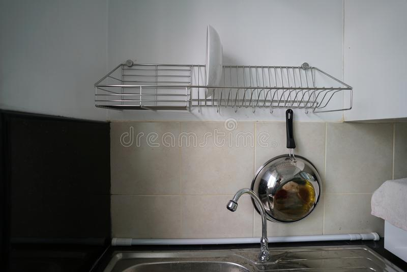 White dishes and drying on a metal dish rack stock photos