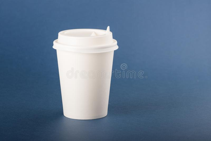 White disposable paper cup with white cap on a blue background.  royalty free stock photo