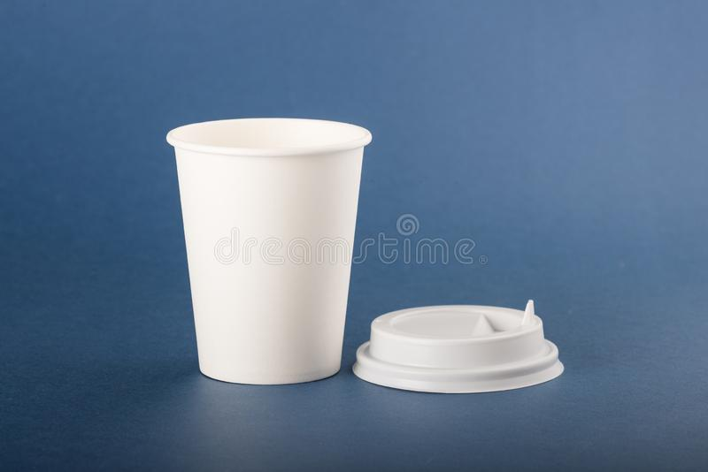 White disposable paper cup with white cap on a blue background.  stock photos