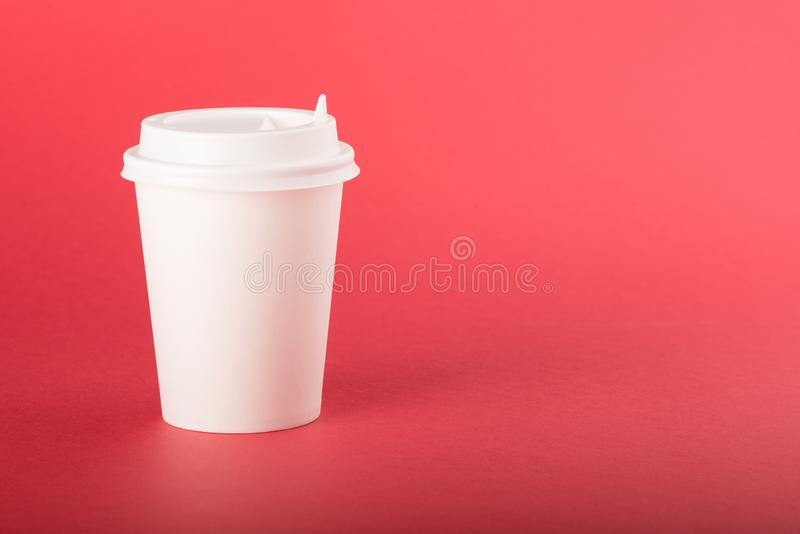 White disposable paper cup with white cap on a red background.  royalty free stock photo