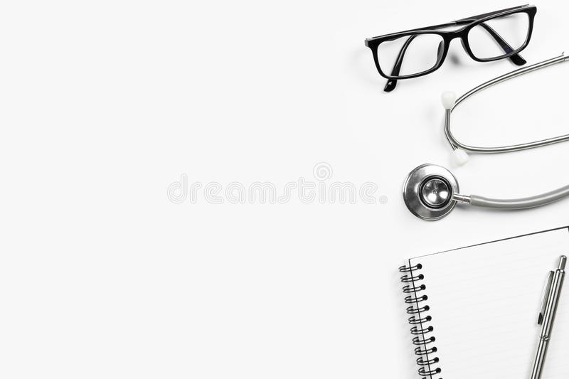 White doctor desk with stethoscope notebook with pen and eye glasses. Top view with copy space, flat lay.  royalty free stock images