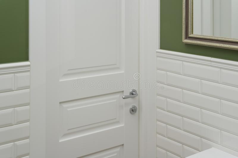 White door in the bathroom toilet room. Background green painted wall covered with decorative ceramic tiles with white glossy bric royalty free stock photos