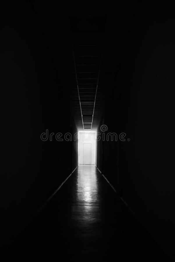 White door at the end of a black long corridor, mystic royalty free stock photos