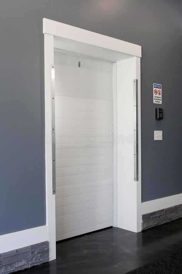 White door entrance secret lock and digital electronic touchscreen keypad security and entry door lock. Part of the room- white door entrance secret lock and royalty free stock photos