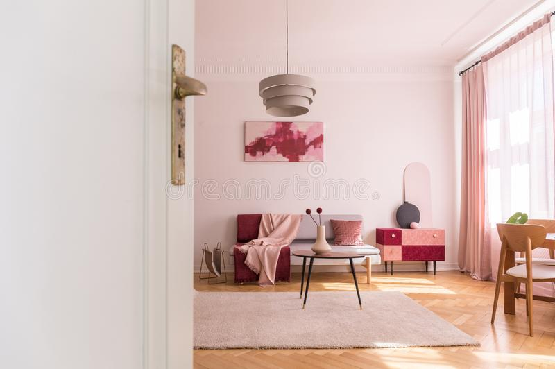 White door of living room with poster above couch near table with flowers on pink carpet. Real photo. White door of living room with poster above couch near royalty free stock photos