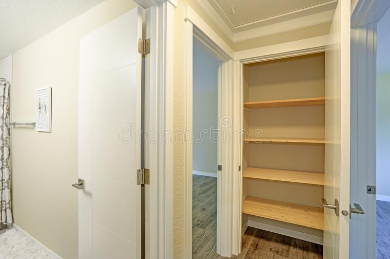 White door opens to a kitchen pantry filled with wooden shelves stock images