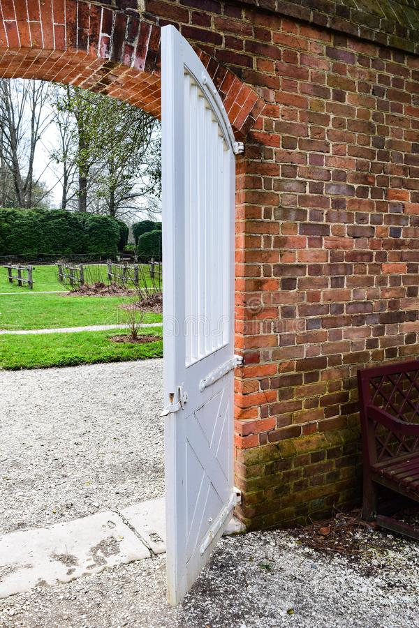 White Door to a Garden. In Colonial Williamsburg, it is hard to miss the little details that keep the feel of the visit truly authentic stock photos