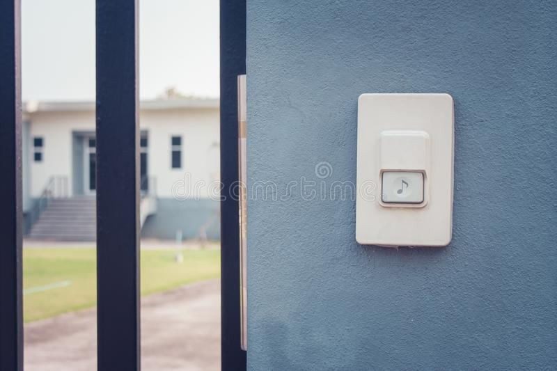 White doorbell or buzzer button on concrete wall beside doorway with house in the background. royalty free stock photos