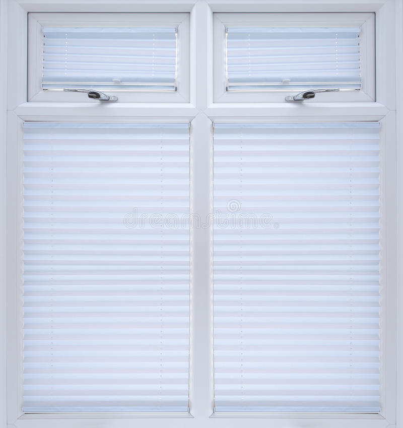 White double glazed window. White UPVC double glazed window with blinds and lockable top openers stock photo