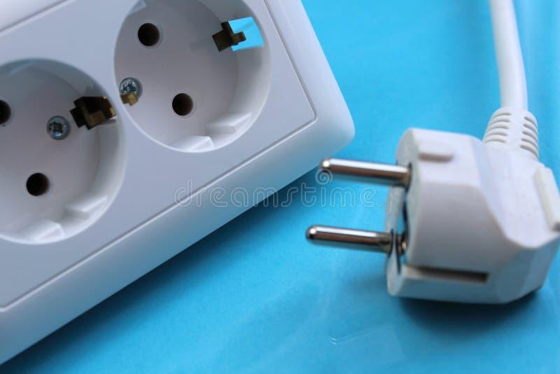 White double socket and plug on blue background royalty free stock photo