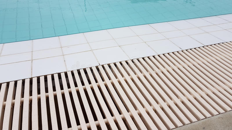 White drainage rail with white tile beside the swimming pool. Background stock photos