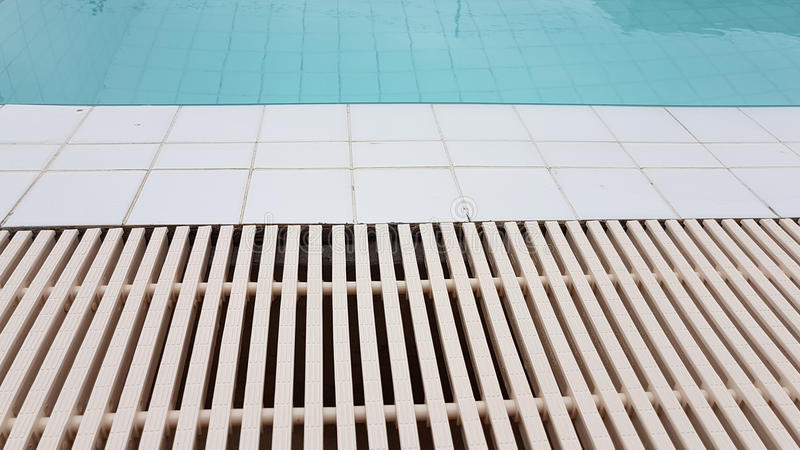 White drainage rail with white tile beside the swimming pool. Background royalty free stock photography