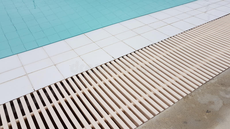 White drainage rail with white tile beside the swimming pool. Background royalty free stock photo