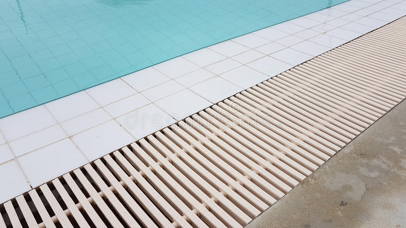 White drainage rail with white tile beside the swimming pool. Background royalty free stock image