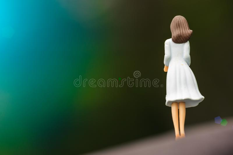 White dress girl toy figure back view in green nature stock images