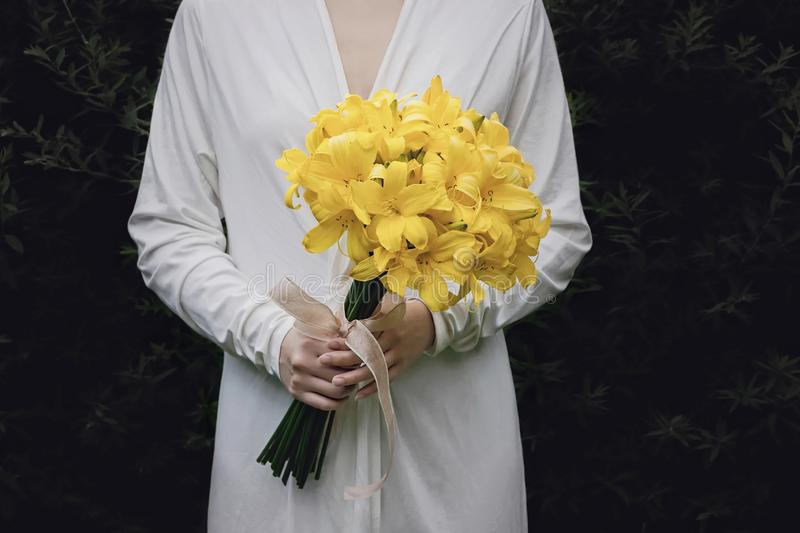 White dress woman holding yellow lily flower bouquet. White wedding dress woman holding yellow lily flower bouquet royalty free stock photo