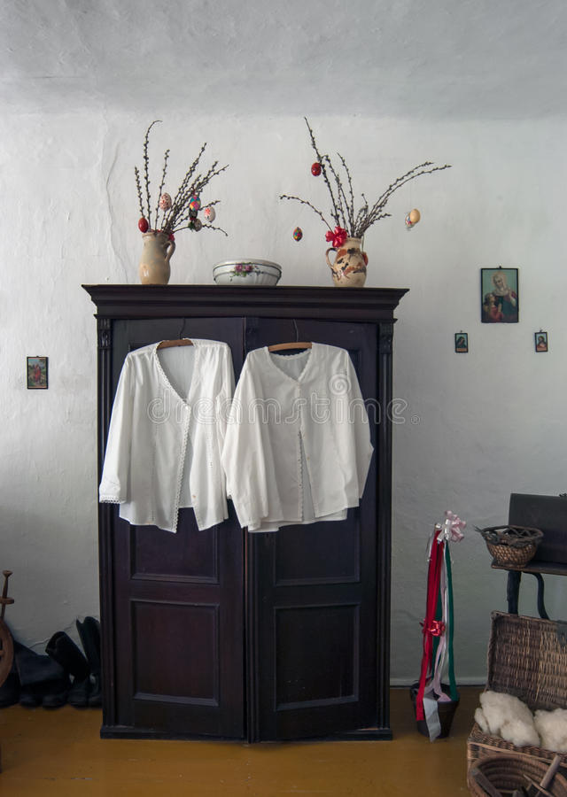White Dresses hanging On cabinet. White Ornate Dresses with Hangers hanging on homemade cabinet stock photography