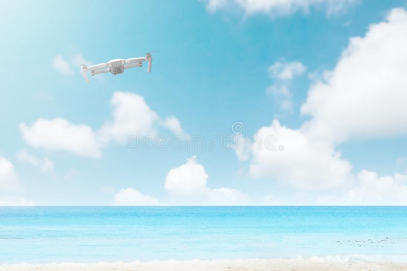 White drone with camera flying over the beach with blue ocean royalty free stock photo