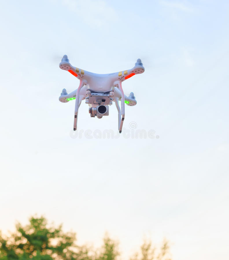 White drone hovering in a bright blue sky stock image